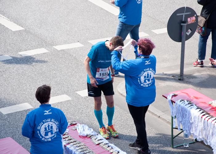 Die Läufer werden mit einer Medaille beim Haspa Marathon Hamburg geehrt