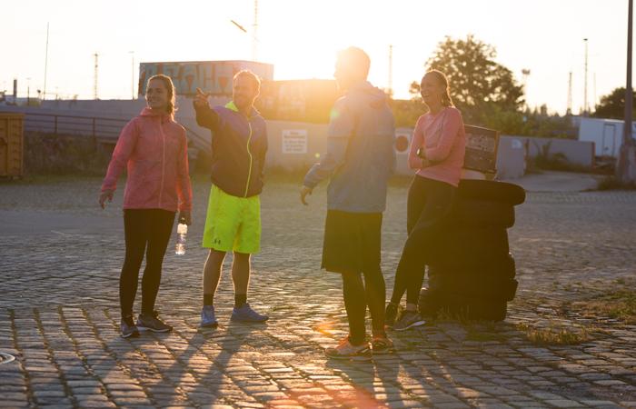 Läufer mit bunten Laufsachen von Asics udn Nike gehen zusammen laufen