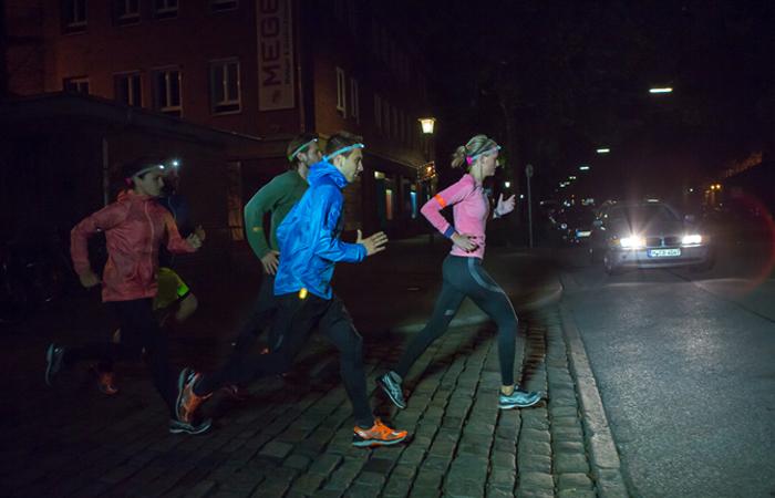 Gruppe Läufer läuft in der Stadt über eine Straße mit Stirnlampen