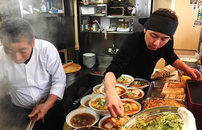 Essen am einer Bude am Fischmarkt. Es gibt Ramen-Suppe