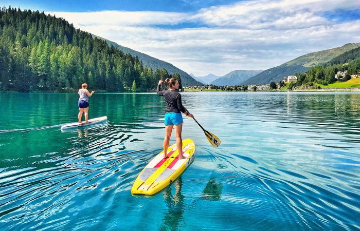 SUP auf dem Davosersee, zwei Mädchen machen Stand Up Paddeling