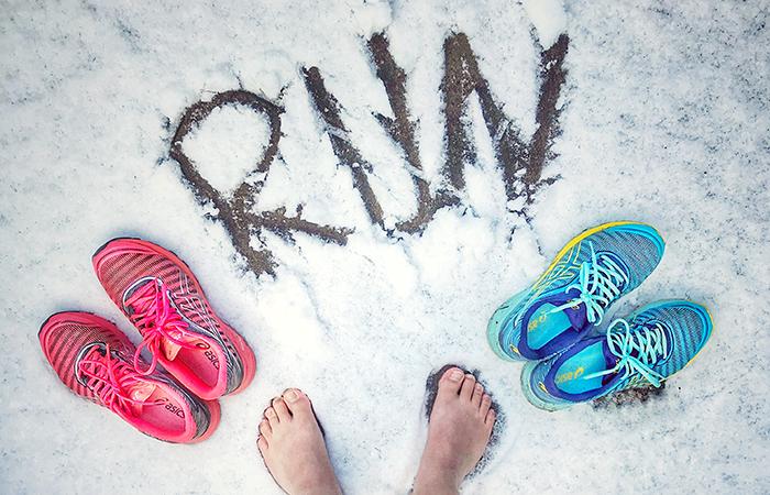 Füße im Schnee. Barfuß im Schnee laufen. Laufschuhe von Asics
