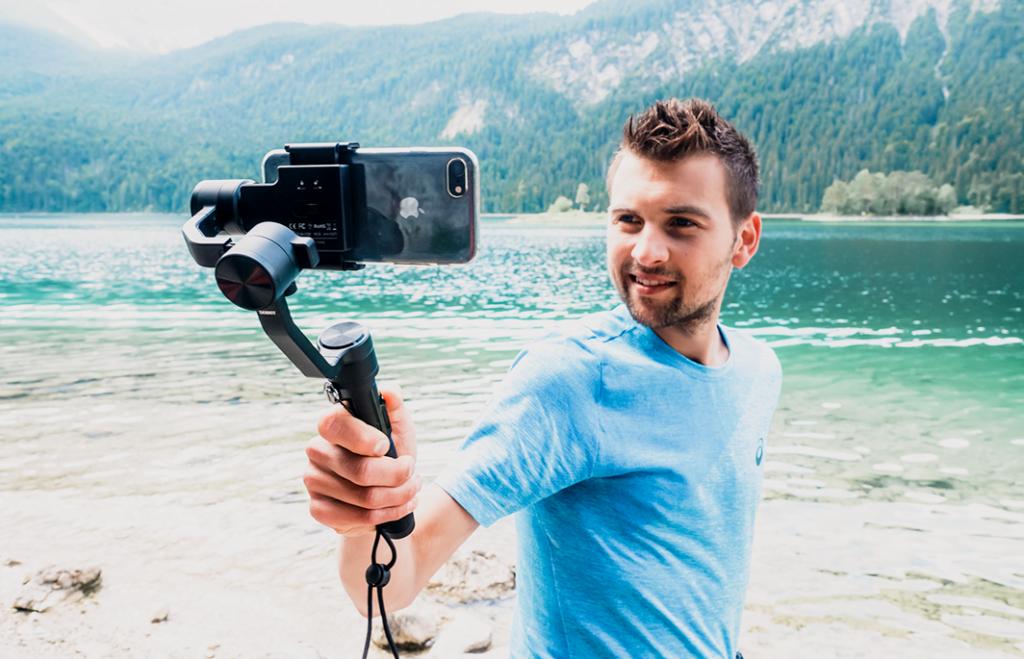 Mann am See mit einem Gimbal, er macht Selfies mit seinem Smartphone, Eibsee in Bayern