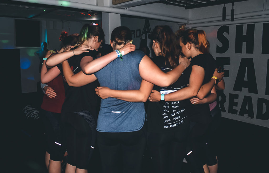 Frauen bei der SFR Academy zum Selbstverteidigungskurs. Sie stehen im Kreis und umarmen sich.