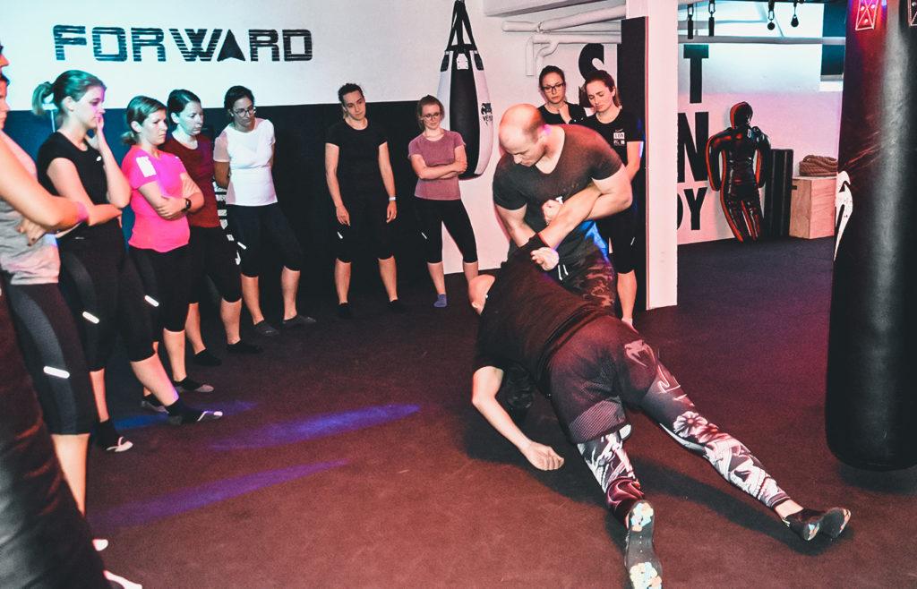 Arthur Bax, der Trainer in der SFR Academy demonstriert den Teilnehmerinnen des Selbstverteidiungskurs welche Techniken man anwendet, um sich im Ernstfall zu schützen. Die Teilnehmerinnen schauen interessiert zu.