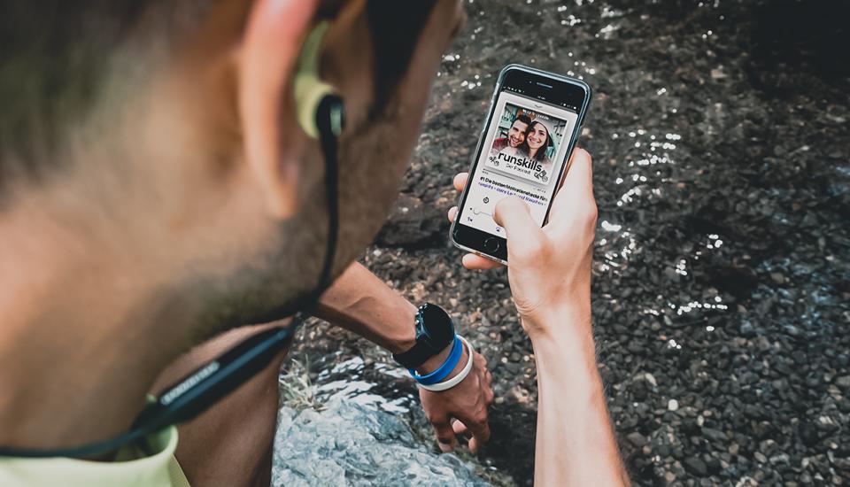 Läufer hört Podcast am Smartphone mit Bluetooth-Kophörern. Er sitzt dabe am Wasser. Auf dem Display sieht man das Cover des runskills-Podcasts.