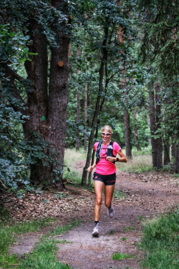 Frau mit pinken T-Shirt und Sonnenbrille läuft durch den Wald.