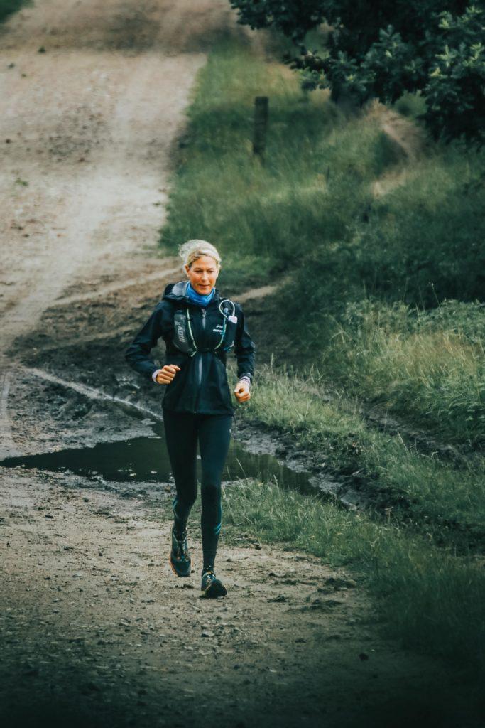 Judith Havers läuft durch den Wald mit Trinkrucksack